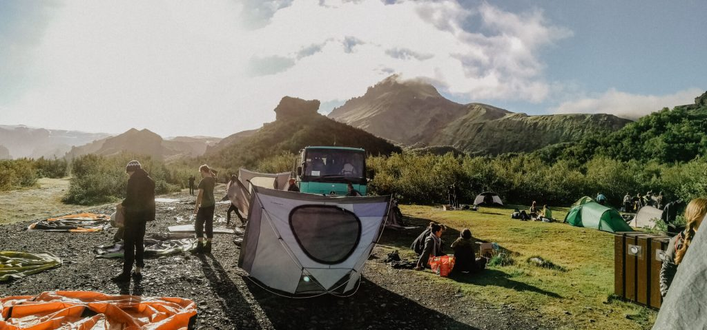Der Campingplatz im Sonnenaufgang umgeben von Birken am Fuß der Berge im Thorsmörk Islands.